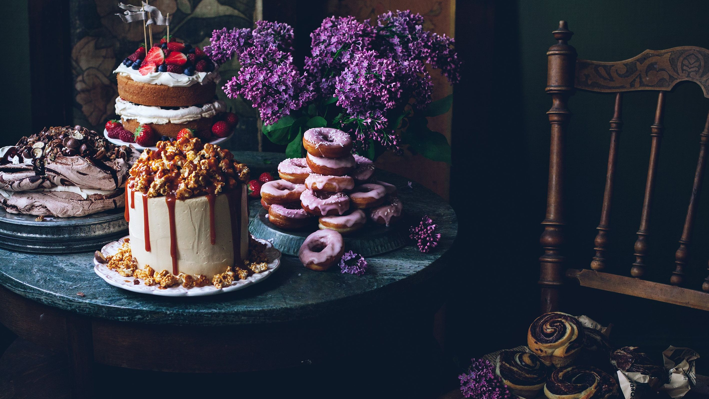 A table display with cakes, meringue, iced donuts and pastries.